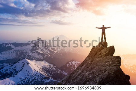 Adventure, Explore and Lifestyle Concept Composite. Adventurous Man Hiker With Hands Up on top of a Steep Rocky Cliff. Sunset or Sunrise. Landscape Taken from Washington, USA. Royalty-Free Stock Photo #1696934809