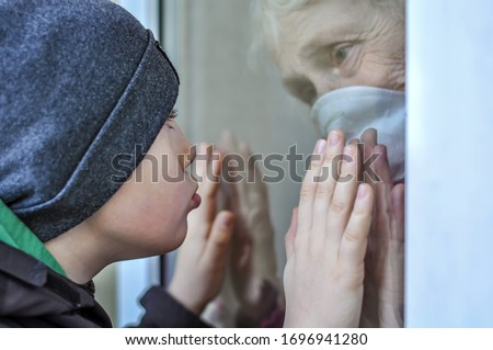 A sad grandmother mature woman in a respiratory mask communicates with grandchild through a window. Elderly quarantined, isolated. Pandemic coronavirus covid-19. Older people. Visit to grandma #1696941280