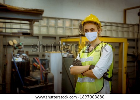 Portrait woman worker under inspection and checking production process on factory station by wearing safety mask face to protect for pollution and virus in factory. #1697003680