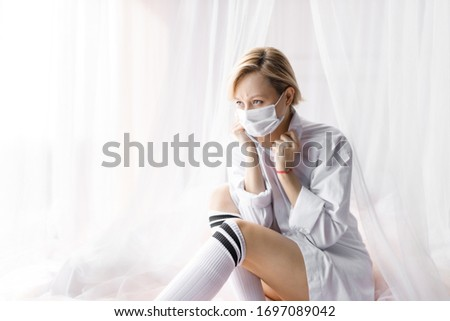 Illness girl on home quarantine. Girl in protective medical masks sits on windowsill and looks out window. Virus protection, coronavirus pandemic, prevention epidemic. #1697089042
