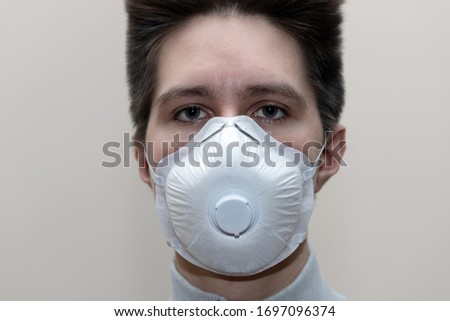 Young man in a medical mask smiles, portrait, close up, health care concept #1697096374