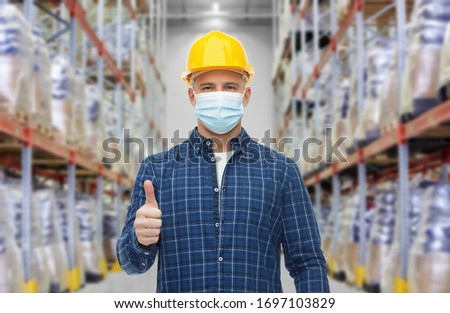 health protection, safety and pandemic concept - male worker in safety helmet wearing face protective medical mask over warehouse background #1697103829