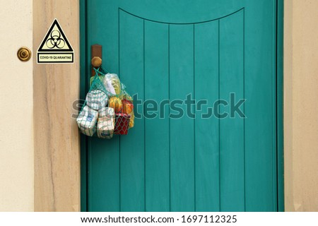 Food delivery during the quarantine. Shopping bag with Merchandise, goods and food is hanging at the front door, warning sign, message COVID-19 Quarantine. coronavirus neighborhood Assistance #1697112325