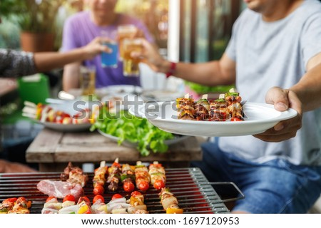 A man with a barbecue plate at a party between friends. Food, people and family time concept. #1697120953