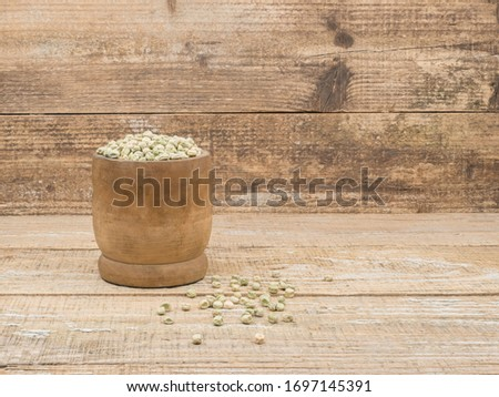 Dry pea grains for planting in the ground on wooden background. Wooden mortar peas. Grain seedlings scattered on the boards. #1697145391
