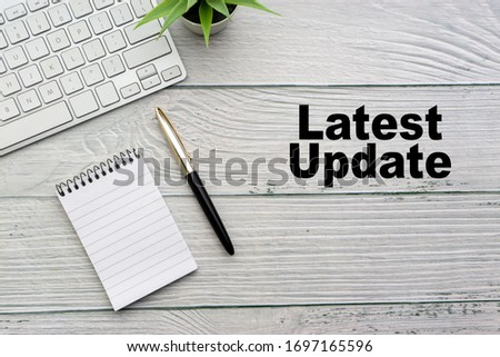 LATEST UPDATE text with notepad, keyboard, decorative vase and fountain pen on wooden background. Business and copy space concept