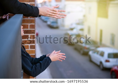 hands clapping on a balcony overlooking a street with the lights on Royalty-Free Stock Photo #1697195536