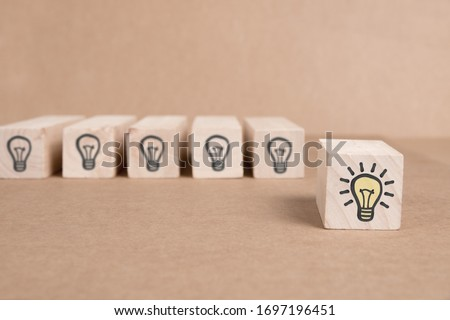 Wooden block group with dark and shining light bulbs imprinted. Shining one separated from the rest of the group. Idea, Innovation, Standing Out and Success Concept. #1697196451