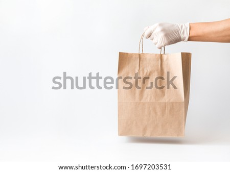 Сoncept of safe home delivery in a pandemic. Coronavirus 2019-nCov Protection. Courier  Paper bag hand in medical glove.Copy space . #1697203531