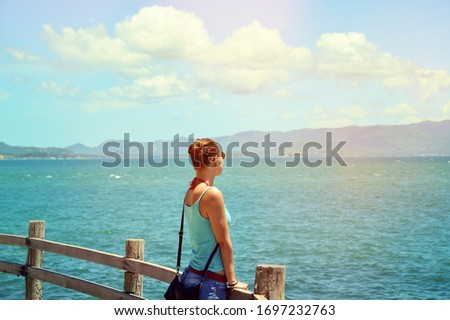 Girl on the beach looks into the distance. #1697232763