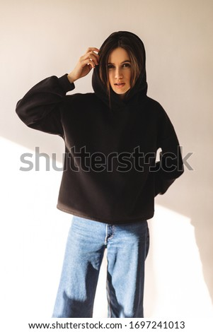 Beautiful girl dressed in sports clothes and hold hood. Brunette with long hair posing. She is dress in black hoodie. Sexy woman look sensual and she is look at camera. Girl wear hood on her hand . #1697241013