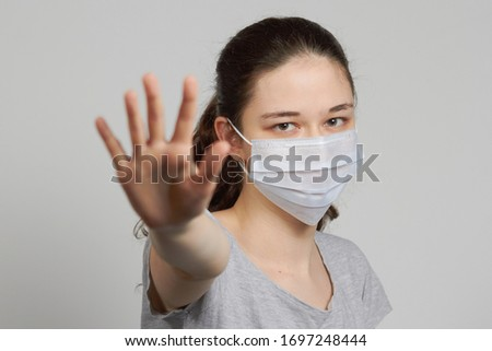 a girl in a mask shows a stop gesture fearing for the health of people #1697248444