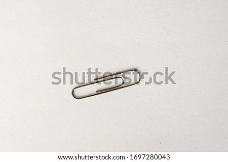 A silver paperclip on a white background. #1697280043
