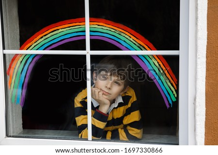 Lovely school kid boy with rainbow painted with colorful window color during pandemic coronavirus quarantine. Child painting rainbows around the world with the words Let's all be well. #1697330866