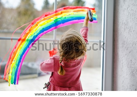 Adoralbe little toddler girl with rainbow painted with colorful window color during pandemic coronavirus quarantine. Child painting rainbows around the world with the words Let's all be well. Royalty-Free Stock Photo #1697330878