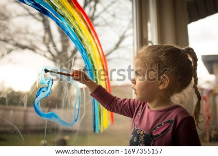 Little, serious, focused girl painting blue color on window, during social distancing and self isolation, let's all be well rainbow symbol #1697355157