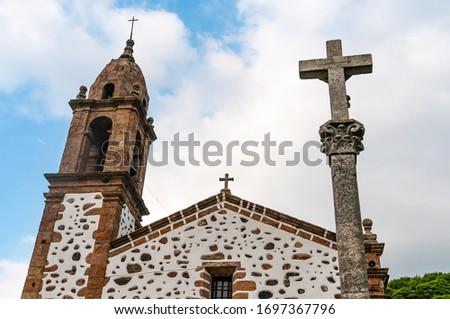SAN ANDRES DE TEIXIDO, LA CORUÑA, GALICIA, SPAIN - JULY 5, 2019: Church and stone cross #1697367796