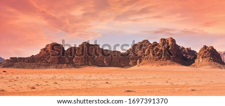 Planet Mars like landscape - Photo of Wadi Rum desert in Jordan with red pink sky above, this location was used as set for many science fiction movies #1697391370