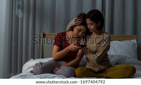 Young beautiful Asian woman comforting her sad girl friend that get bad news from smartphone. Woman hugging and consoling depressed friend at night. Social issue, mental health and friendship concept. #1697404792
