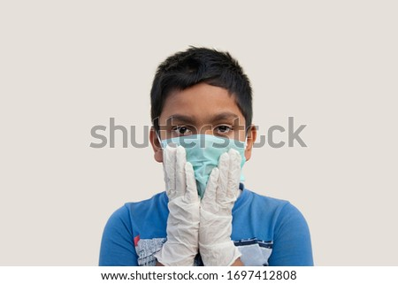 Boy wearing rubber glove putting on protective mask  #1697412808