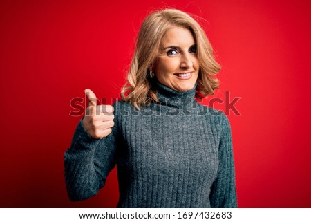 Middle age beautiful blonde woman wearing casual turtleneck sweater over red background doing happy thumbs up gesture with hand. Approving expression looking at the camera showing success.
