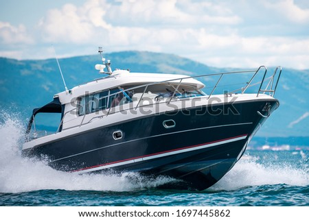 A black hull speedboat racing by sea Royalty-Free Stock Photo #1697445862