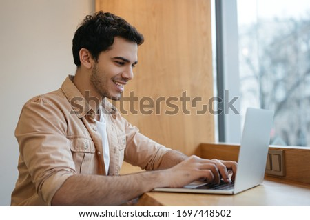 Indian freelancer working from home. Successful asian business man using laptop computer, typing on keyboard, watching training courses, planning start up in office