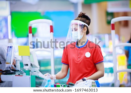 female supermarket cashier in medical protective mask and face shield working at supermarket. covid-19 spreading outbreak   #1697463013