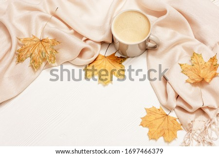 Autumn cozy composition with dried leaves of maple and pastel beige scarf, cup of coffee on white wooden background. Autumn, fall concept. Flat lay, top view, copy space. #1697466379