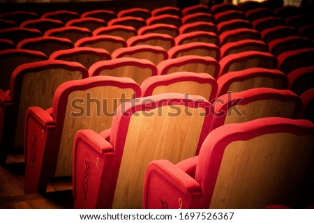A close up of row of red empty theatre chairs shot from the back with dark vignette #1697526367