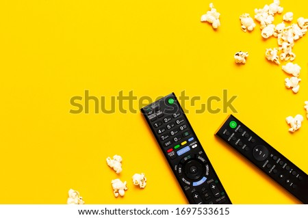 Black TV, audio remote control and popcorn on bright yellow background flat lay top view copy space. Minimalistic background with a remote control, watching a movie series, set-top boxes, audio system #1697533615