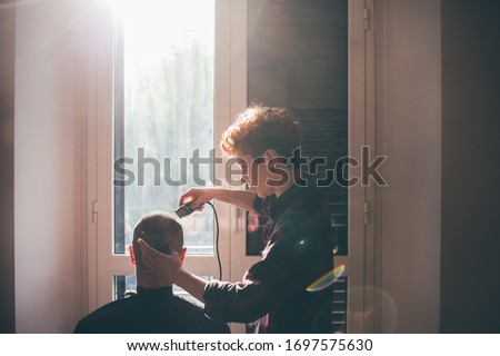 Young woman cutting the hair of a men indoor at home - har care, hair cut, self isolation concept #1697575630