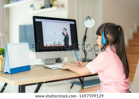 Asian girl student video conference e-learning with teacher on computer in living room at home. Homeschooling and distance learning ,online ,education and internet protect from COVID-19 viruses. #1697599129