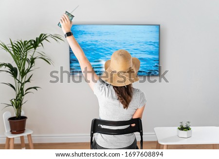 Woman at home pretending to be on the beach. TV screen. 2020 summer quarantine travel. Stay home #1697608894