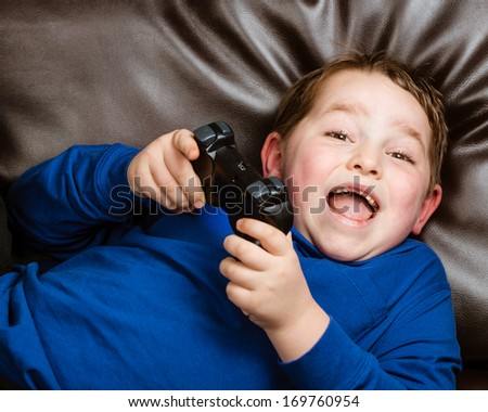 Young boy playing video game laying on couch at home #169760954
