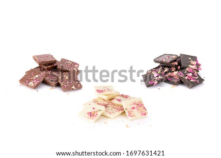 Crushed handmade organic milk, white and dark chocolates with rose oil from Damascena rose and sprinkled with rose leaves. Isolated on white background. #1697631421
