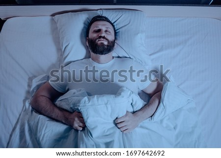 A lone bearded dark-haired man sleeps soundly lying on his back at night in bed. The general plan from above, white bedding, a bedroom, self-isolation. One Royalty-Free Stock Photo #1697642692