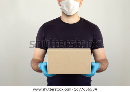 Delivery man holding cardboard boxes in medical rubber gloves and mask. copy space. Fast and free Delivery transport . Online shopping and Express delivery . Quarantine. Mockup  #1697656534