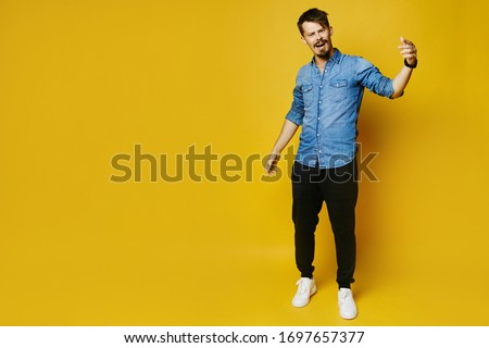Yes, he did it. Stylish happy bearded man raising hands and shouting, posing in full length on the yellow background, isolated with copy space on the left #1697657377