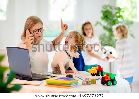 Mother working from home with kids. Homeschooling and home office.  Quarantine, closed school, coronavirus outbreak. Self isolation and social distancing. Children make noise and disturb mom at work.  #1697673277