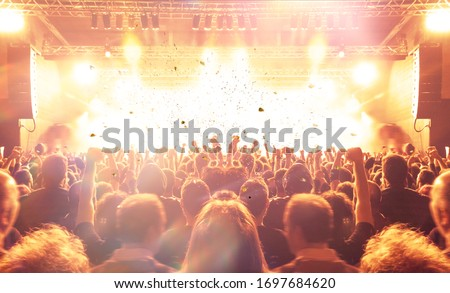 Music festival crowd,concert spectators in front of a bright stage with live music #1697684620