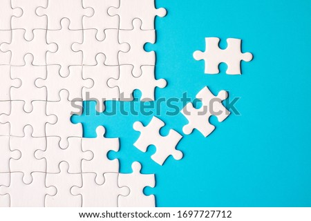 Many white jigsaw puzzle on blue background - idea solution concept. #1697727712