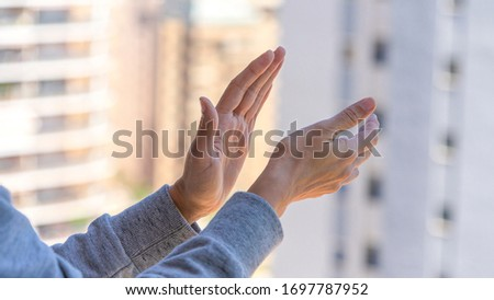 Woman hands applauding medical staff from their balcony. People in Spain clapping gratitude on balconies and windows in support of health workers, doctors and nurses during the Coronavirus pandemic Royalty-Free Stock Photo #1697787952