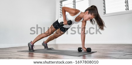 Home fitness plank row workout Asian woman training arms doing rowing exercise planking with dumbbell weights inside. one arm row exercising indoors. Panoramic banner. Royalty-Free Stock Photo #1697808010