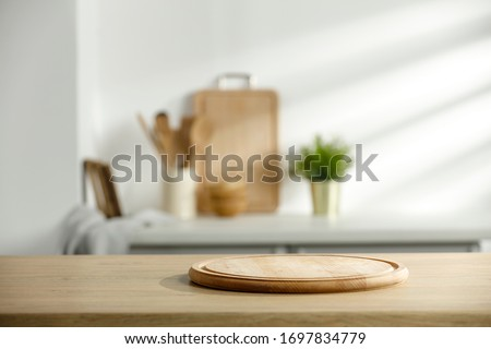 Table background of free space and kitchen interior.White wall with shadows and sunny warm morning time.Copy space for your composition.  #1697834779