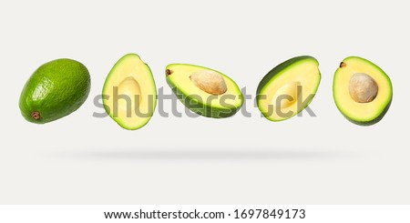 Creative layout with ripe flying avocado halves on light background. Healthy food, diet, tropical exotic fruit, trendy food product. Minimalistic summer food concept. Organic avocado. Pop art design Royalty-Free Stock Photo #1697849173