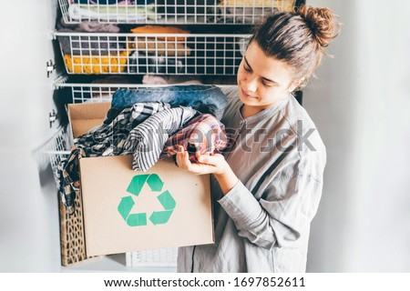 Recycle clothes concept. Young woman with recycling box full clothes. #1697852611