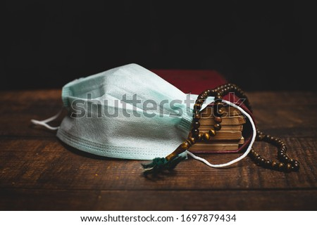 Holy Al Quran, prayer beads and protective mask on wooden table. Coronavirus Covid-19 quarantine muslim prayer concept. Royalty-Free Stock Photo #1697879434