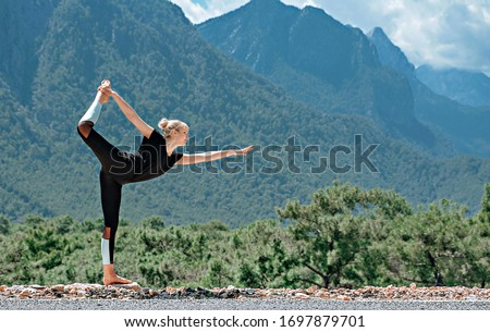 Woman doing yoga poses outside and beautiful view of mountains and sky with clouds #1697879701