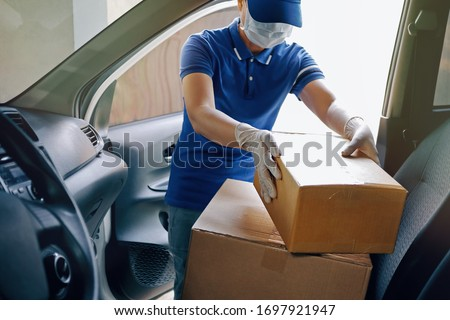 Delivery services courier during the Coronavirus (COVID-19) pandemic, courier wearing medical mask and latex gloves for safety protection from virus infection working with cardboard boxes on van seat. #1697921947